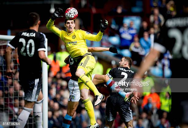 Jordan Ayew of Aston Villa is challenged by Thibaut Courtois of Chelsea during the Barclays Premier League match between Aston Villa and Chelsea at...