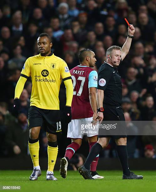 Jordan Ayew of Aston Villa is shown a red card by referee Jonathan Moss during the Barclays Premier League match between West Ham United and Aston...