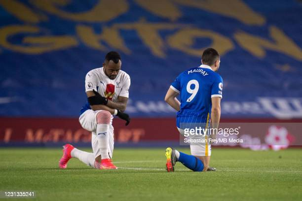 Jordan Ayew of Crystal Palace and Neal Maupay of Brighton & Hove Albion take a knee during the Premier League match between Brighton & Hove Albion...