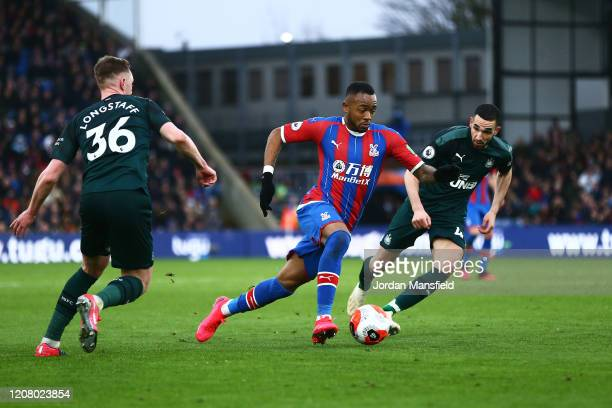 Jordan Ayew of Crystal Palace avoids a tackle from Nabil Bentaleb and Sean Longstaff of Newcastle United during the Premier League match between...