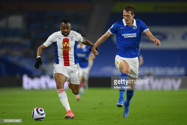 Jordan Ayew of Crystal Palace is challenged by Dan Burn of Brighton & Hove Albionduring the Premier League match between Brighton & Hove Albion and...