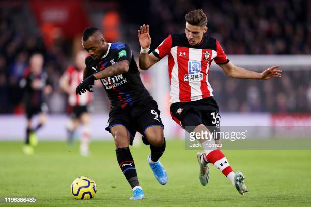 Jordan Ayew of Crystal Palace is challenged by Jan Bednarek of Southampton during the Premier League match between Southampton FC and Crystal Palace...