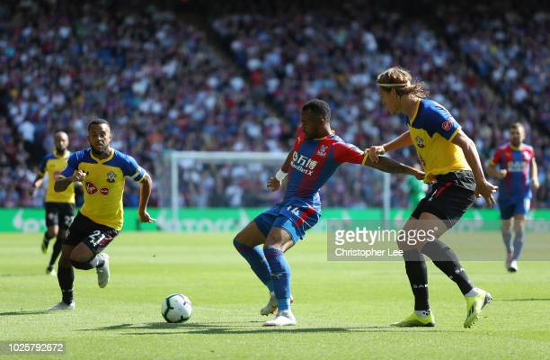 Jordan Ayew of Crystal Palace is challenged by Jannik Vestergaard of Southampton during the Premier League match between Crystal Palace and...