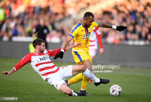 Jordan Ayew of Crystal Palace is challenged by Matthew Blair of Doncaster Rovers during the FA Cup Fifth Round match between Doncaster Rovers and...