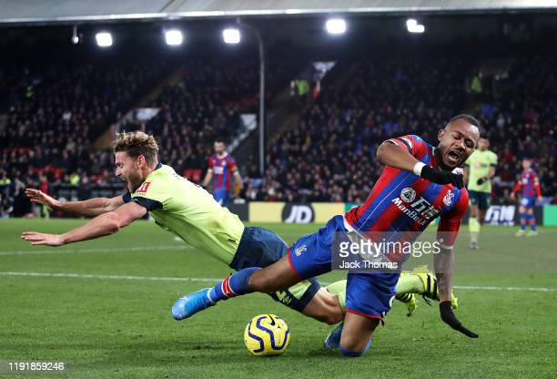 Jordan Ayew of Crystal Palace is challenged by Simon Francis of AFC Bournemouth during the Premier League match between Crystal Palace and AFC...