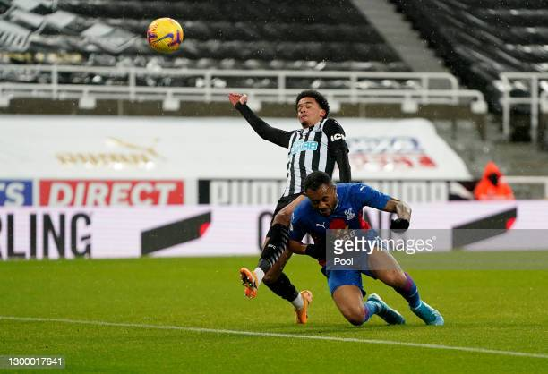 Jordan Ayew of Crystal Palace wins a header ahead of Jamal Lewis of Newcastle United during the Premier League match between Newcastle United and...