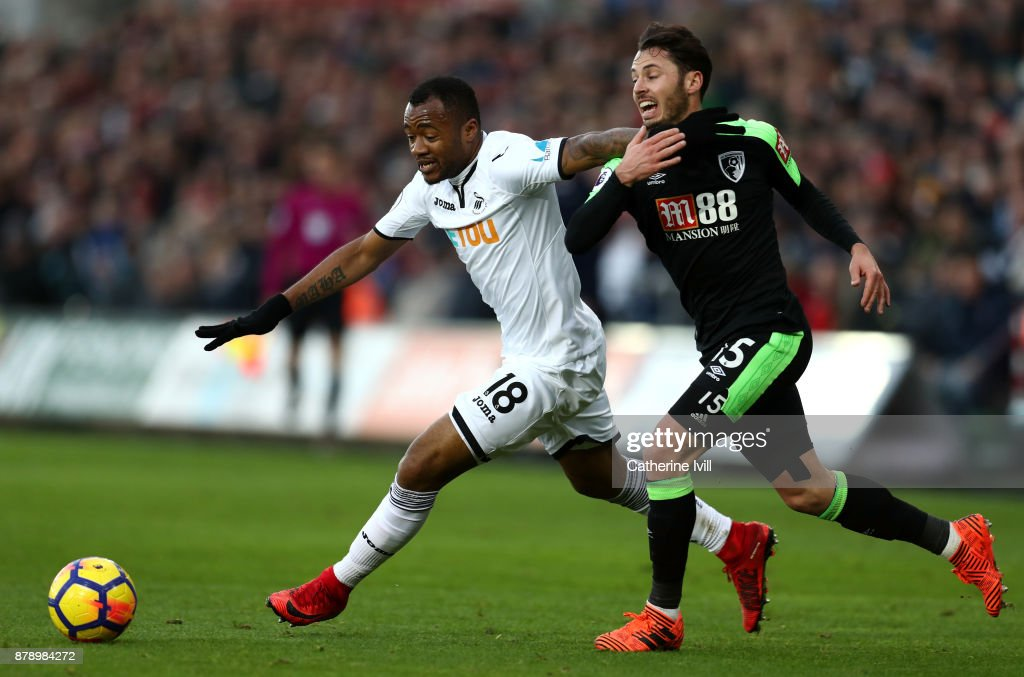 Jordan Ayew of Swansea City and Adam Smith of AFC Bournemouth battle for possession during the Premier League match between Swansea City and AFC Bournemouth at Liberty Stadium on November 25, 2017 in Swansea, Wales.