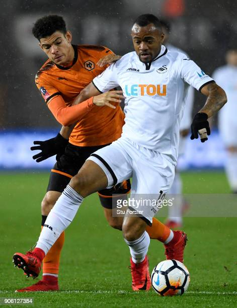 Jordan Ayew of Swansea City and Morgan GibbsWhite of Wolverhampton Wanderers in action during The Emirates FA Cup Third Round Replay between Swansea...