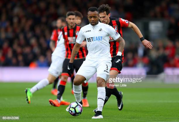 Jordan Ayew of Swansea City attempts to take the ball away from Charlie Daniels of AFC Bournemouth during the Premier League match between AFC...