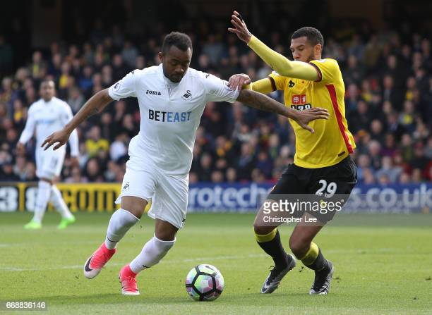 Jordan Ayew of Swansea City attempts to take the ball past Etienne Capoue of Watford during the Premier League match between Watford and Swansea City...