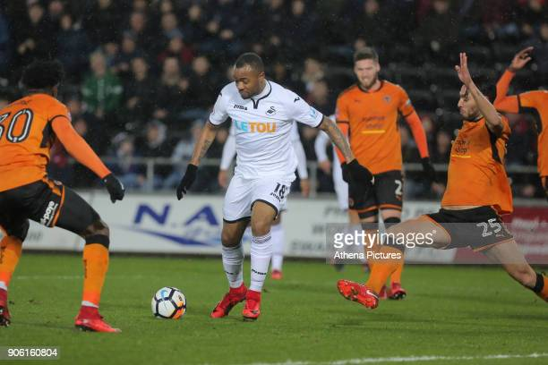 Jordan Ayew of Swansea City avoids a challenge by Roderick Miranda of Wolverhampton Wanderers to score his opening goal during the Emirates FA Cup...