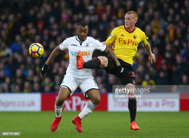 Jordan Ayew of Swansea City battles for possesion with Ben Watson of Watford during the Premier League match between Watford and Swansea City at...