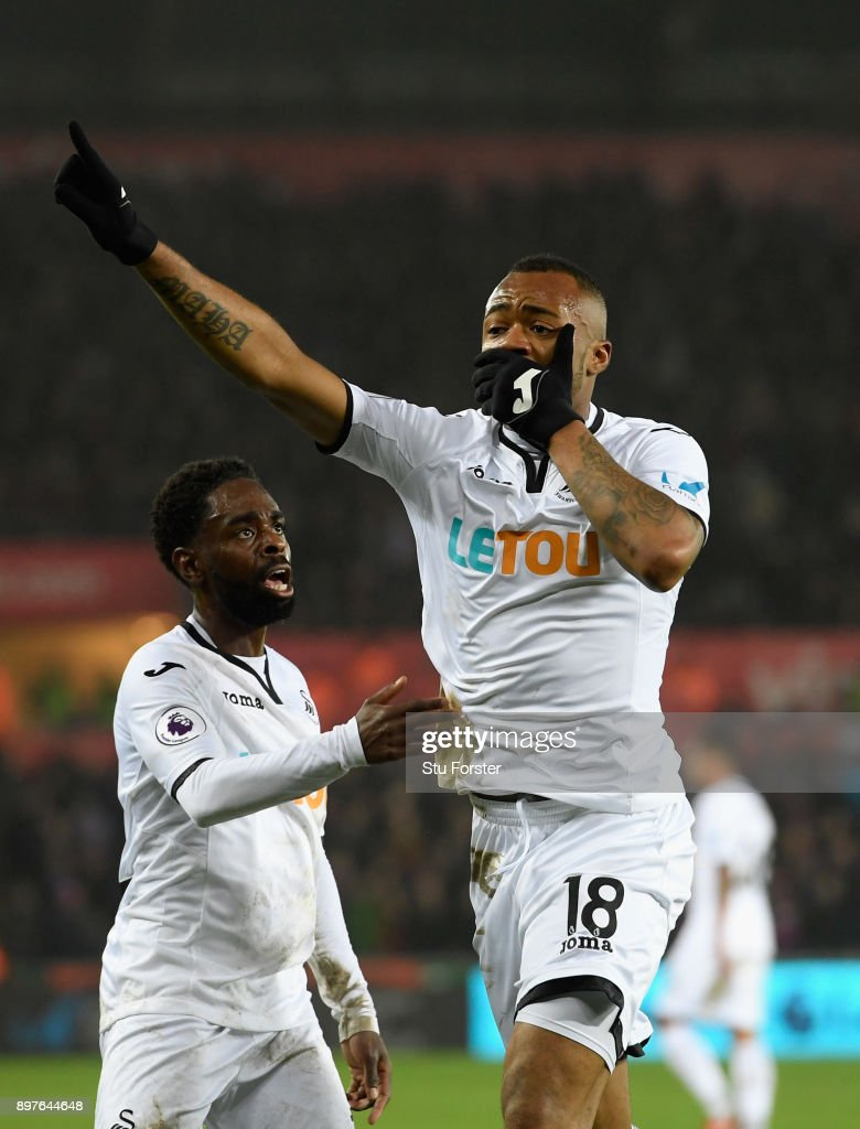 Jordan Ayew of Swansea City celebrates with Nathan Dyer (l) after scoring his sides first goal during the Premier League match between Swansea City and Crystal Palace at Liberty Stadium on December 23, 2017 in Swansea, Wales.