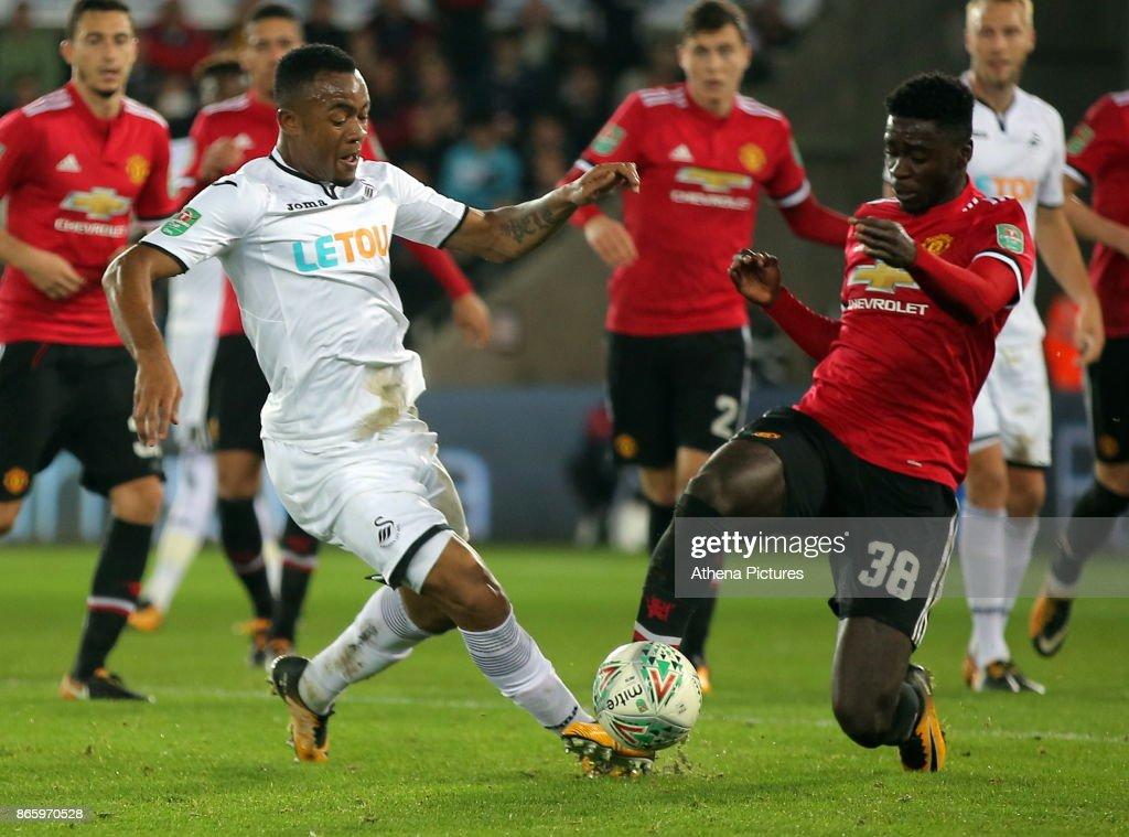 Jordan Ayew of Swansea City challenged by Axel Tuanzebe of Manchester United during the Carabao Cup Fourth Round match between Swansea City and Manchester United at The Liberty Stadium on October 24, 2017 in Swansea, Wales.