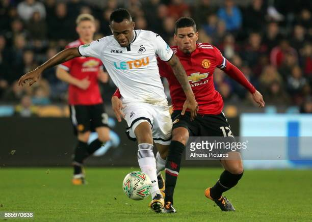Jordan Ayew of Swansea City challenged by Chris Smalling of Manchester United during the Carabao Cup Fourth Round match between Swansea City and...