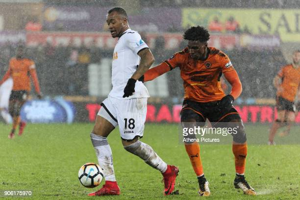Jordan Ayew of Swansea City challenged by Kortney Hause of Wolverhampton Wanderers during the Emirates FA Cup match between Swansea and Wolverhampton...