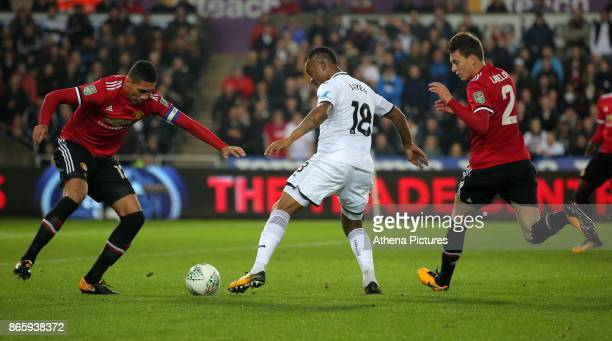 Jordan Ayew of Swansea City charges forward past Chris Smalling and Victor Lindelof of Manchester United during the Carabao Cup Fourth Round match...