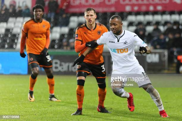 Jordan Ayew of Swansea City closely marked by Barry Douglas of Wolverhampton Wanderers during the Emirates FA Cup match between Swansea and...