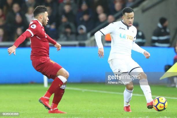 Jordan Ayew of Swansea City is challenged by Alex OxladeChamberlain of Liverpool during the Premier League match between Swansea City and Liverpool...