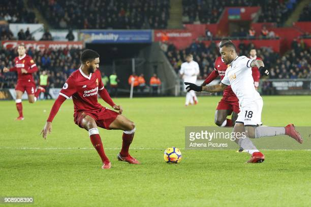 Jordan Ayew of Swansea City is challenged by Joe Gomez of Liverpoold during the Premier League match between Swansea City and Liverpool at the...