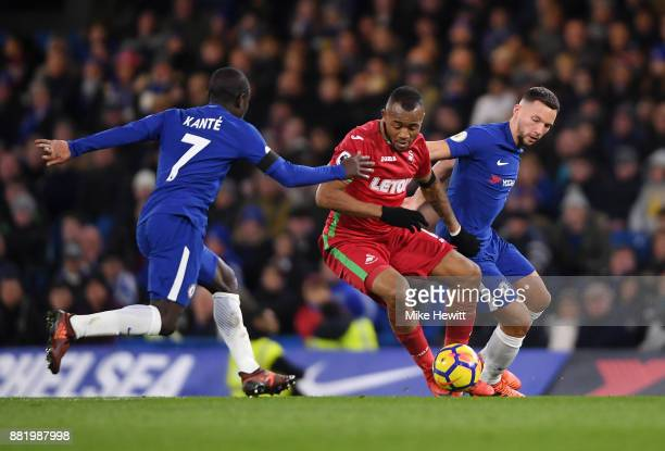 Jordan Ayew of Swansea City is challenged by N'Golo Kante of Chelsea and Danny Drinkwater of Chelsea during the Premier League match between Chelsea...
