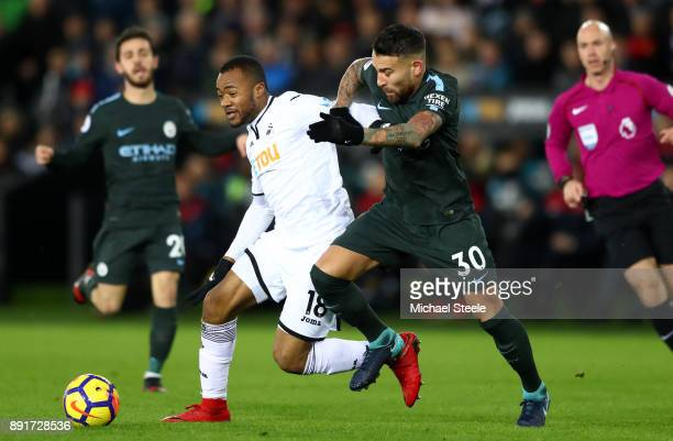 Jordan Ayew of Swansea City is challenged by Nicolas Otamendi of Manchester City during the Premier League match between Swansea City and Manchester...