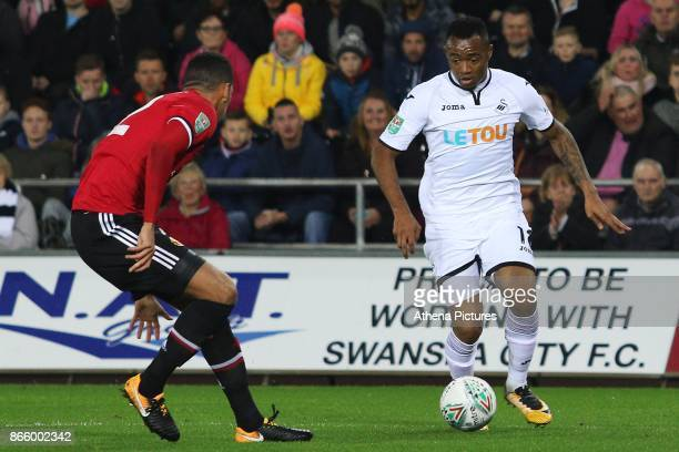 Jordan Ayew of Swansea City is marked by Chris Smalling of Manchester United during the Carabao Cup Fourth Round match between Swansea City and...