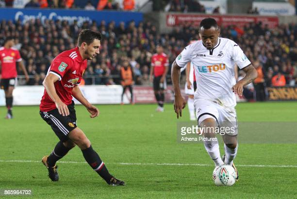 Jordan Ayew of Swansea City is marked by Matteo Darmian of Manchester United during the Carabao Cup Fourth Round match between Swansea City and...