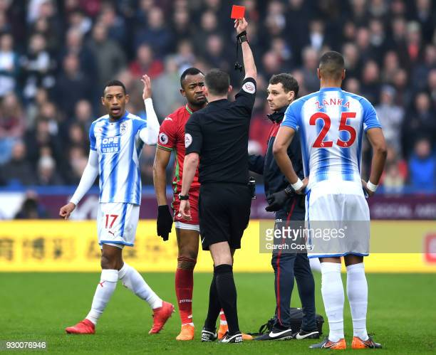 Jordan Ayew of Swansea City is shown a red card by referee Michael Oliver during the Premier League match between Huddersfield Town and Swansea City...