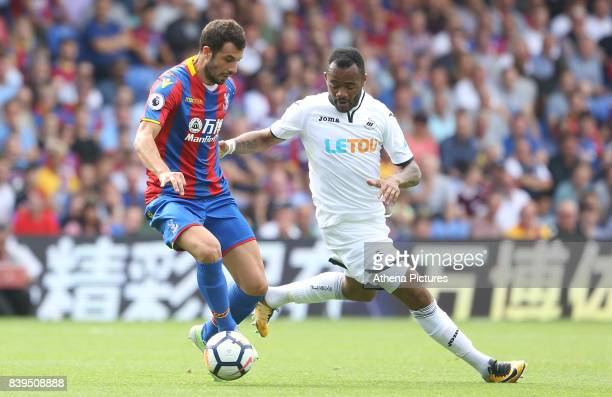 Jordan Ayew of Swansea City marks Luka Milivojevic of Crystal Palace during the Premier League match between Crystal Palace and Swansea City at...