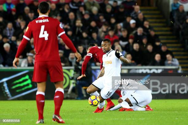 Jordan Ayew of Swansea City plays on as Emre Can of Liverpool is tackled by Leroy Fer during the Premier League match between Swansea City and...