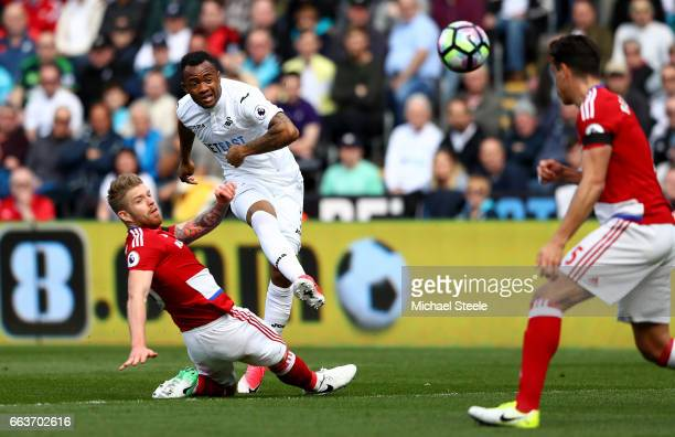Jordan Ayew of Swansea City shoots as Adam Clayton of Middlesbrough attempts to block during the Premier League match between Swansea City and...