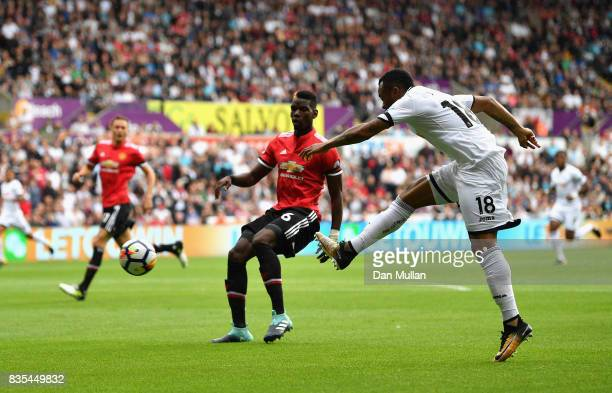 Jordan Ayew of Swansea City shoots as Paul Pogba of Manchester United attempts to block during the Premier League match between Swansea City and...