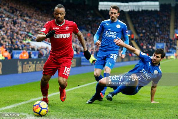 Jordan Ayew of Swansea is marked by Aleksandar Dragovic of Leicester City during the Premier League match between Leicester City and Swansea City at...
