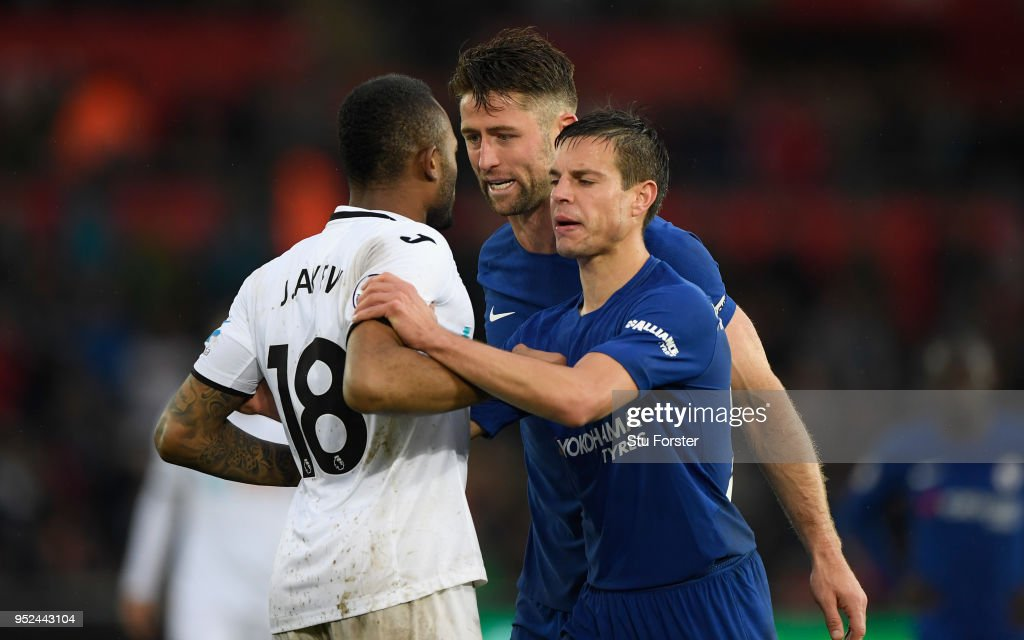 Jordan Ayew of Swansea is seperated from Gary Cahill (c) by his team mate Cesar Azpilicueta after a heated exchange during the Premier League match between Swansea City and Chelsea at Liberty Stadium on April 28, 2018 in Swansea, Wales.