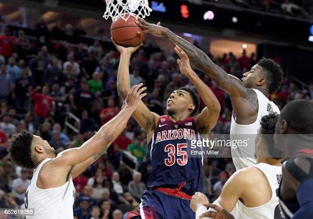 Jordan Bell of the Oregon Ducks blocks a shot by Allonzo Trier of the Arizona Wildcats as Tyler Dorsey of the Ducks defends during the championship...