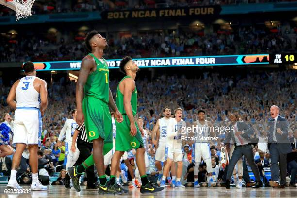 Jordan Bell and Tyler Dorsey of the Oregon Ducks look on as the North Carolina Tar Heels celebrate during the 2017 NCAA Men's Final Four Semifinal at...