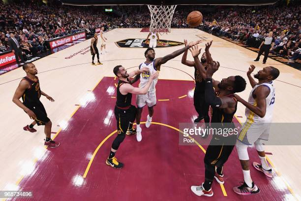 Jordan Bell of the Golden State Warriors battles for a rebound with Kevin Love Tristan Thompson and Jeff Green of the Cleveland Cavaliers in the...