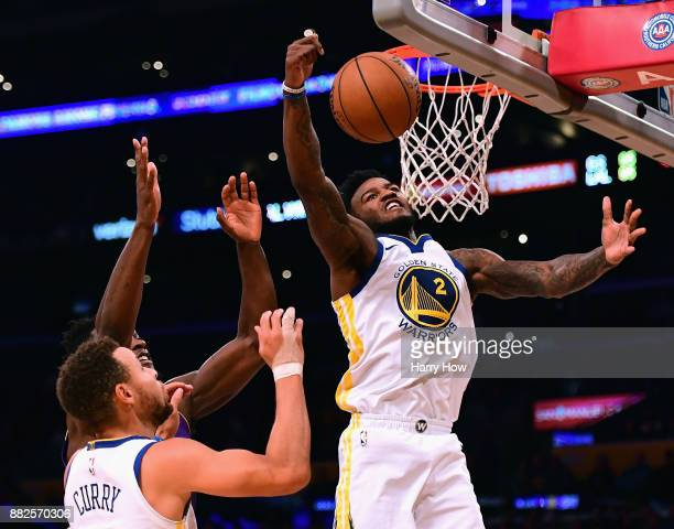 Jordan Bell of the Golden State Warriors grabs a rebound in front of Julius Randle of the Los Angeles Lakers as Stephen Curry watches during a 127123...