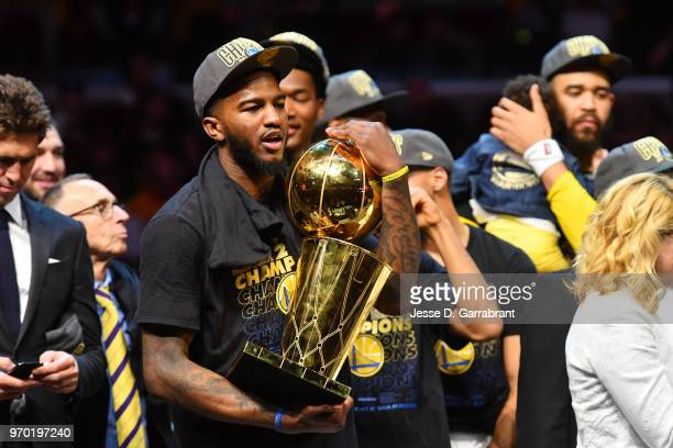 Jordan Bell of the Golden State Warriors holds the Larry O'Brien Championship trophy after defeating the Cleveland Cavaliers in Game Four of the 2018...