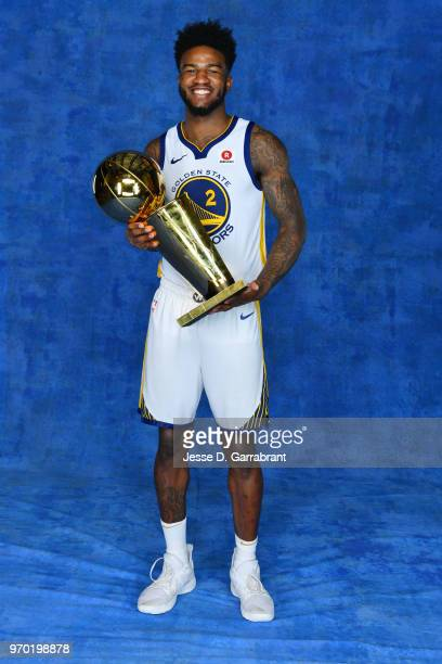 Jordan Bell of the Golden State Warriors poses for a portrait with the Larry O'Brien Championship trophy after defeating the Cleveland Cavaliers in...
