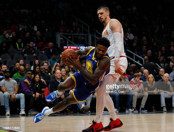 Jordan Bell of the Golden State Warriors slips and fall as he drives against Alex Len of the Atlanta Hawks at State Farm Arena on December 3 2018 in...