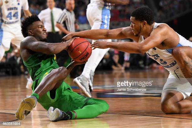 Jordan Bell of the Oregon Ducks and Kennedy Meeks of the North Carolina Tar Heels both grab at the ball during the 2017 NCAA Photos via Getty Images...