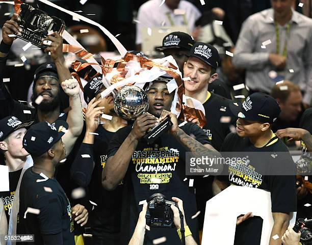 Jordan Bell of the Oregon Ducks holds the championship trophy as he and his teammates celebrate their 8857 victory over the Utah Utes to win the...