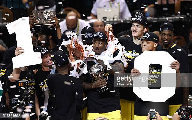 Jordan Bell of the Oregon Ducks holds the championship trophy as he and his teammates celebrate their 88-57 victory over the Utah Utes to win the...