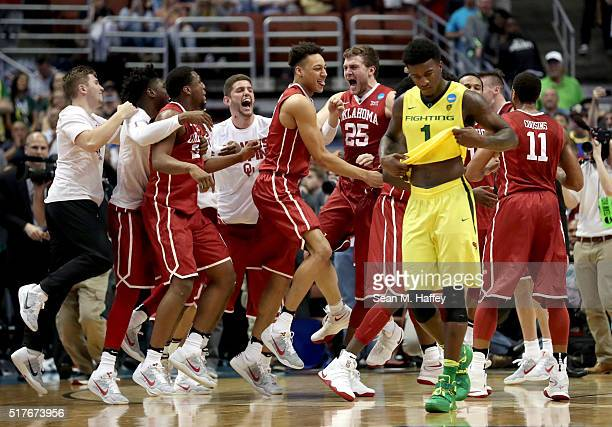 Jordan Bell of the Oregon Ducks walks off as CJ Cole Isaiah Cousins and Khadeem Lattin of the Oklahoma Sooners celebrate their 8068 victory against...