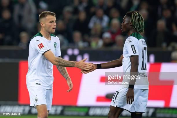 Jordan Beyer of Borussia Moenchengladbach and Manu Kone of Borussia Moenchengladbach gestures during the Bundesliga match between Borussia...