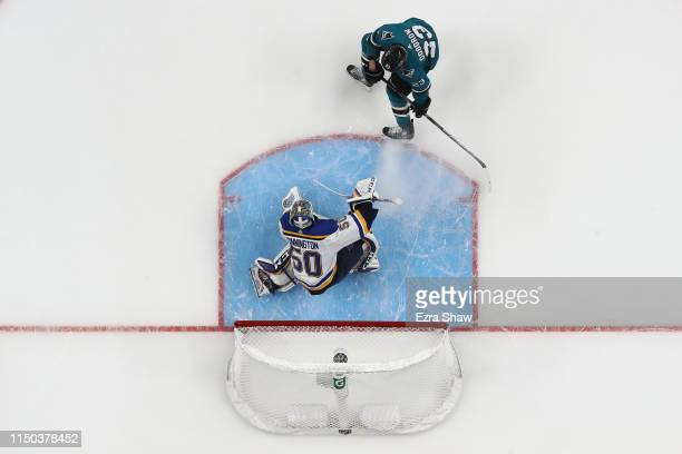 Jordan Binnington of the St Louis Blues makes a save in front of Barclay Goodrow of the San Jose Sharks in Game Five of the Western Conference Final...