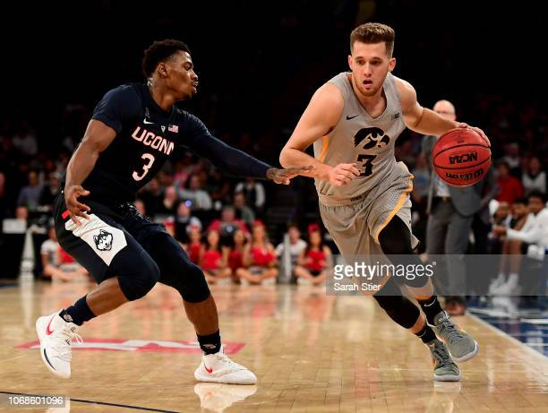 Jordan Bohannon of the Iowa Hawkeyes drives around Alterique Gilbert of the Connecticut Huskies in the second half during the championship game of...