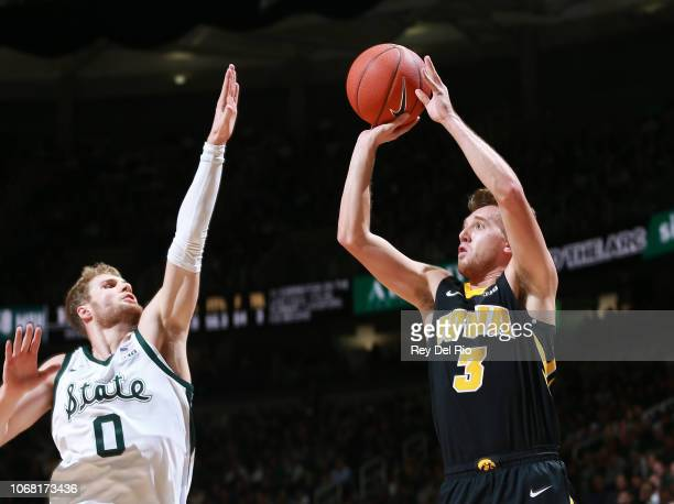 Jordan Bohannon of the Iowa Hawkeyes shoots the ball against Kyle Ahrens of the Michigan State Spartans in the second half at Breslin Center on...